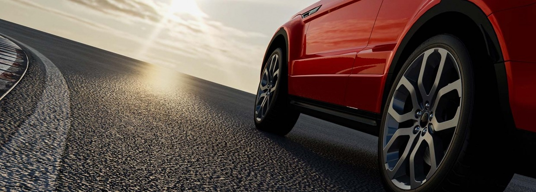 Rode auto rijdt op een weg de zon tegemoet